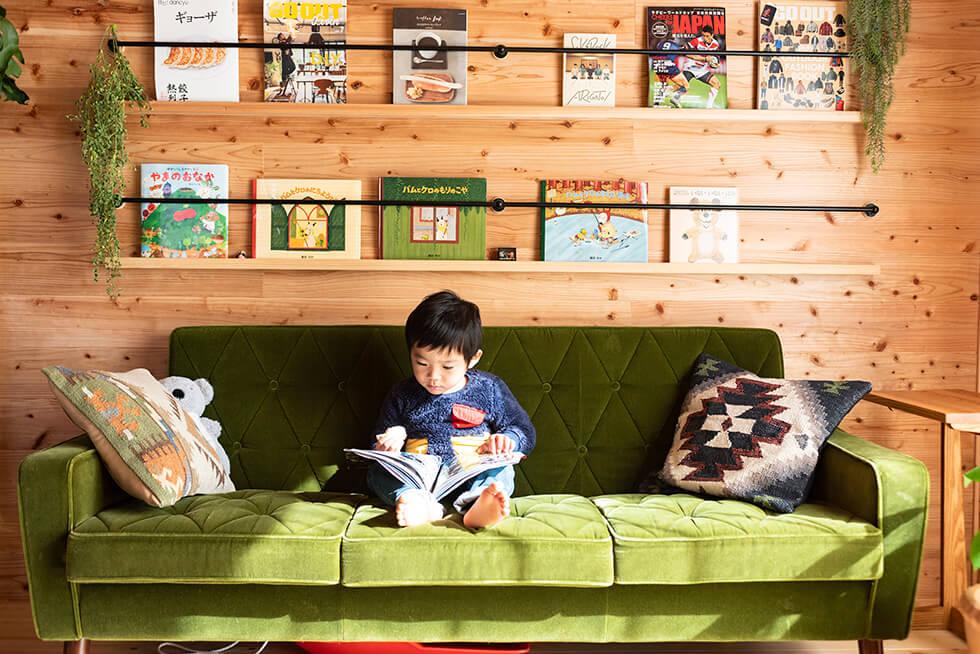 リビングソファで絵本を見る子ども